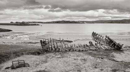 Old fishing boat wreck along Talmine Harbour beach, Sutherland Scotland